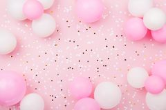 Pastel pink table with frame from balloons and confetti for birthday top view. Flat lay composition. Pastel pink table with frame from balloons and confetti for royalty free stock photo