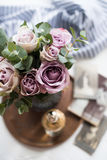 Pastel purple, mauve color fresh summer roses in vase in tray cl. Oseup, vintage style stock photography