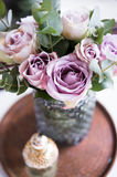 Pastel purple, mauve color fresh summer roses in vase in tray cl. Pastel purple, mauve color fresh summer roses in vase and perfume in tray closeup, vintage stock photography