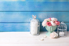 Pastel roses in turquoise vase and candles on white wooden  back Stock Photography