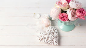 Pastel roses in turquoise vase  and decorative heart on white wo Royalty Free Stock Image