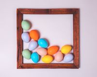 Pastel scattered Easter eggs framed on pink stock photos