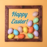 Pastel scattered Easter eggs framed on yellow stock photography