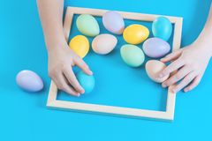 Pastel scattered Easter eggs with kids hands stock photo