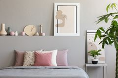 Pastel sheets and cushions placed on double bed in real photo of. Bedroom interior with paintings, handmade clock and decor concept royalty free stock photo