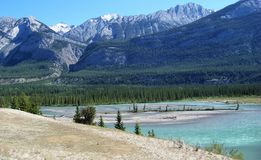 Pastel Tones Accent Wilderness Landscape. Bright blue sky, beige sand and aqua glacial water accent the forest greens and blue grays of nearby mountains of this Stock Photos