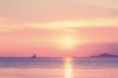 Pastel tropical beach sunset with sailboat Royalty Free Stock Photos