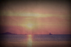 Pastel tropical beach sunset with sailboat in vintage style Stock Image