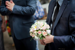 Pastel wedding bouquet with roses in groom's hands. Colorful wedding bouquet with roses  in groom's hands Stock Image
