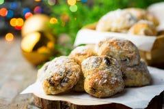A pastelaria alemão tradicional do Natal mini stollen no papel de pergaminho na tabela de madeira da prancha Bolas douradas do ra fotos de stock royalty free