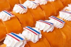 Pastelarias com o esmalte de congelamento alaranjado, o chantiliy e as bandeiras holandesas fotografia de stock