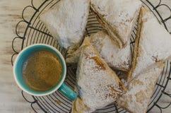Pastelarias flocosos na cremalheira com xícara de café Imagens de Stock