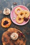 Pastelarias frescas, queques, eclairs, bolos com doce de framboesa A vista da parte superior imagem de stock royalty free