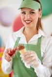 Pasteleiro na loja dos confeitos que põe a bola do gelado dentro Imagens de Stock