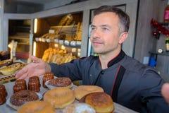 Pasteleiro que mostra bolos da bandeja imagem de stock