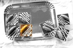 Pasteles coloreados entre los pasteles en blanco y negro Imagen de archivo