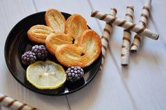 Pasteles con la zarzamora y una rebanada de limón imagen de archivo libre de regalías