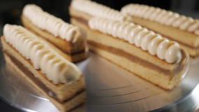 Pasteles con leche condensada y crema en soporte giratorio de la torta en panadería, almacen de video
