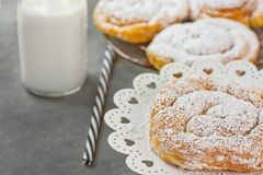 Pasteles daneses del remolino pulverizados en soporte de enfriamiento del estante y de la torta Botella de paja rayada de la lech Foto de archivo libre de regalías