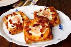 Pasteles daneses, desayuno con el huevo, tocino, queso y pastas de hojaldre Fotografía de archivo libre de regalías