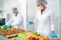 Pasteles de la polvoreda del empleado de la fábrica de la confitería con el azúcar en polvo fotos de archivo