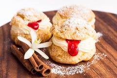 Pasteles de los Choux con crema y cuajada carmesí Fotografía de archivo libre de regalías