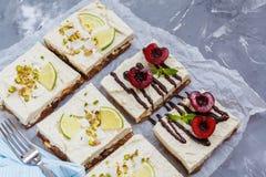 Pasteles de queso crudos del pistacho, del coco, de la cal y de la chocolate-cereza foto de archivo