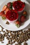 Pasteles de queso de la frambuesa en la placa con el fondo de los granos de café Fotos de archivo libres de regalías