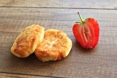 Pasteles de queso en un fondo de madera, desayuno de pasteles de queso con las fresas imagenes de archivo