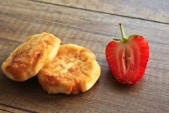 Pasteles de queso en un fondo de madera, desayuno de pasteles de queso con las fresas fotografía de archivo