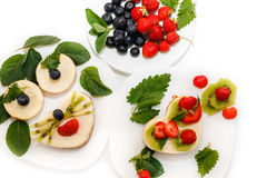 Pasteles de queso sabrosos adornados por la fresa, el arándano y la menta Imagen de archivo libre de regalías