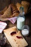 pasteles del desayuno con el atasco y la leche fotografía de archivo libre de regalías