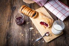 pasteles del desayuno con el atasco y la leche fotografía de archivo