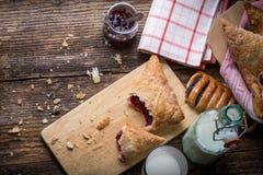 pasteles del desayuno con el atasco y la leche fotos de archivo