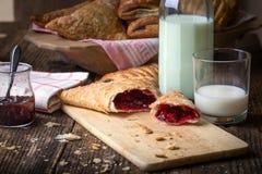 pasteles del desayuno con el atasco y la leche imagen de archivo