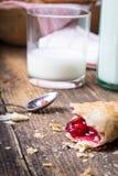 pasteles del desayuno con el atasco y la leche imagenes de archivo