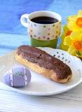 Pasteles del eclair de chocolate con café Imagenes de archivo