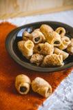 Pasteles dulces con las semillas de amapola en una placa negra foto de archivo
