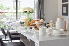 Pasteles en la mesa de comedor artificial blanca del top de la piedra en comedor moderno Fotografía de archivo