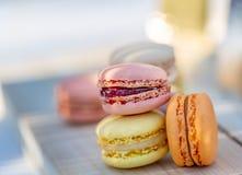 Pasteles franceses coloreados airosos dulces deliciosos Macarons de los dulces por la tarde del verano en una huerta Fondo enmasc imágenes de archivo libres de regalías