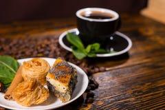 Pasteles gastrónomos con la taza de café en la tabla de madera Fotografía de archivo libre de regalías