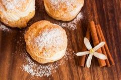 Pasteles hechos en casa de los Choux con crema en el tablero de madera Foto de archivo libre de regalías