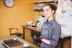 Pasteles sujetos de la profesión y el cocinar mujer caucásica joven con el tatuaje del chef de repostería en la cocina del restau imagen de archivo