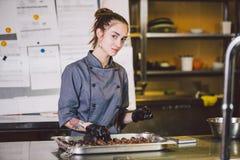 Pasteles sujetos de la profesión y el cocinar mujer caucásica joven con el tatuaje del chef de repostería en la cocina del restau fotografía de archivo