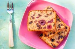 pasteles Una rebanada de la torta con las frutas en una placa rosada Pasa y cereza de la torta de la fruta imágenes de archivo libres de regalías