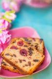 pasteles Una rebanada de la torta con las frutas en una placa rosada Pasa y cereza de la torta de la fruta fotos de archivo
