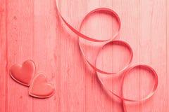 Pastelkleur roze beeld van twee valentijnskaartharten en een spiraal of een krul van zijdelint op een houten raadsachtergrond Con stock foto