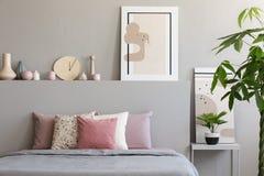 Pastelkleurbladen en kussens op tweepersoonsbed in echte foto die worden geplaatst van royalty-vrije stock foto