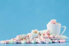 Pastelkleurheemst in een witte kop op een blauwe achtergrond De zoete V.N. Stock Foto's