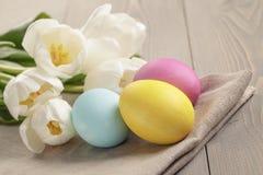 Pastelkleurpaaseieren met tulpen op lijst Stock Foto's